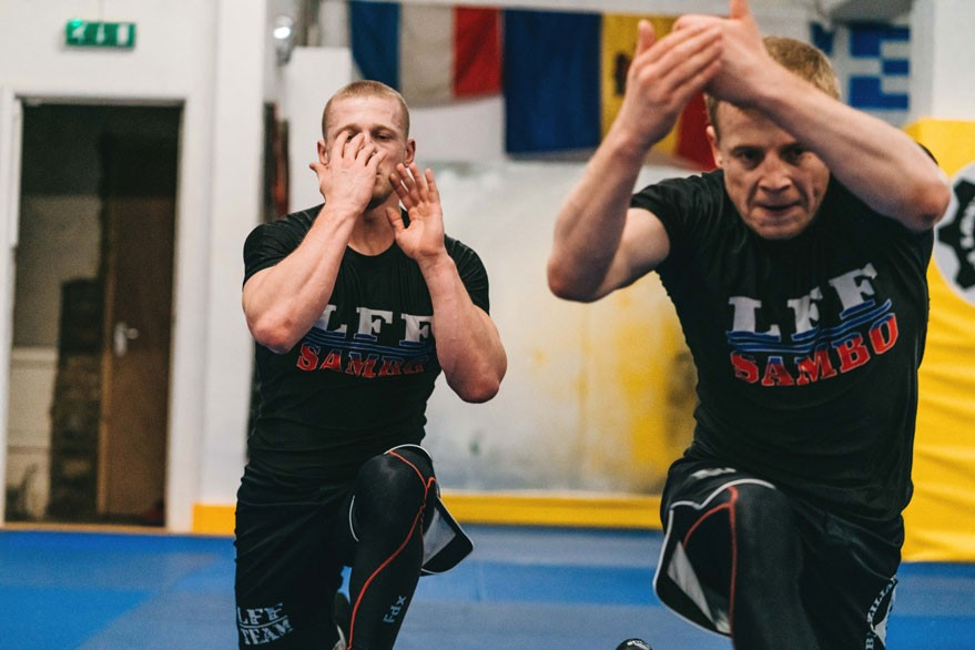 Two very focused male students warm up before a Sambo class with a series of lunges to help with hip rotation. They are both wearing black shorts and rash guards that read 'LFF Sambo'.